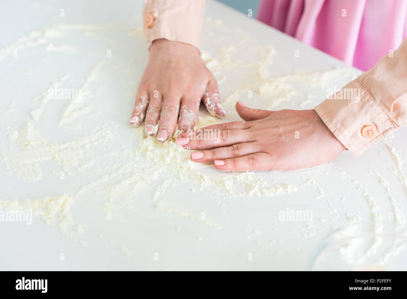 cropped image of woman spreading flour on kitchen counter - Stock Image