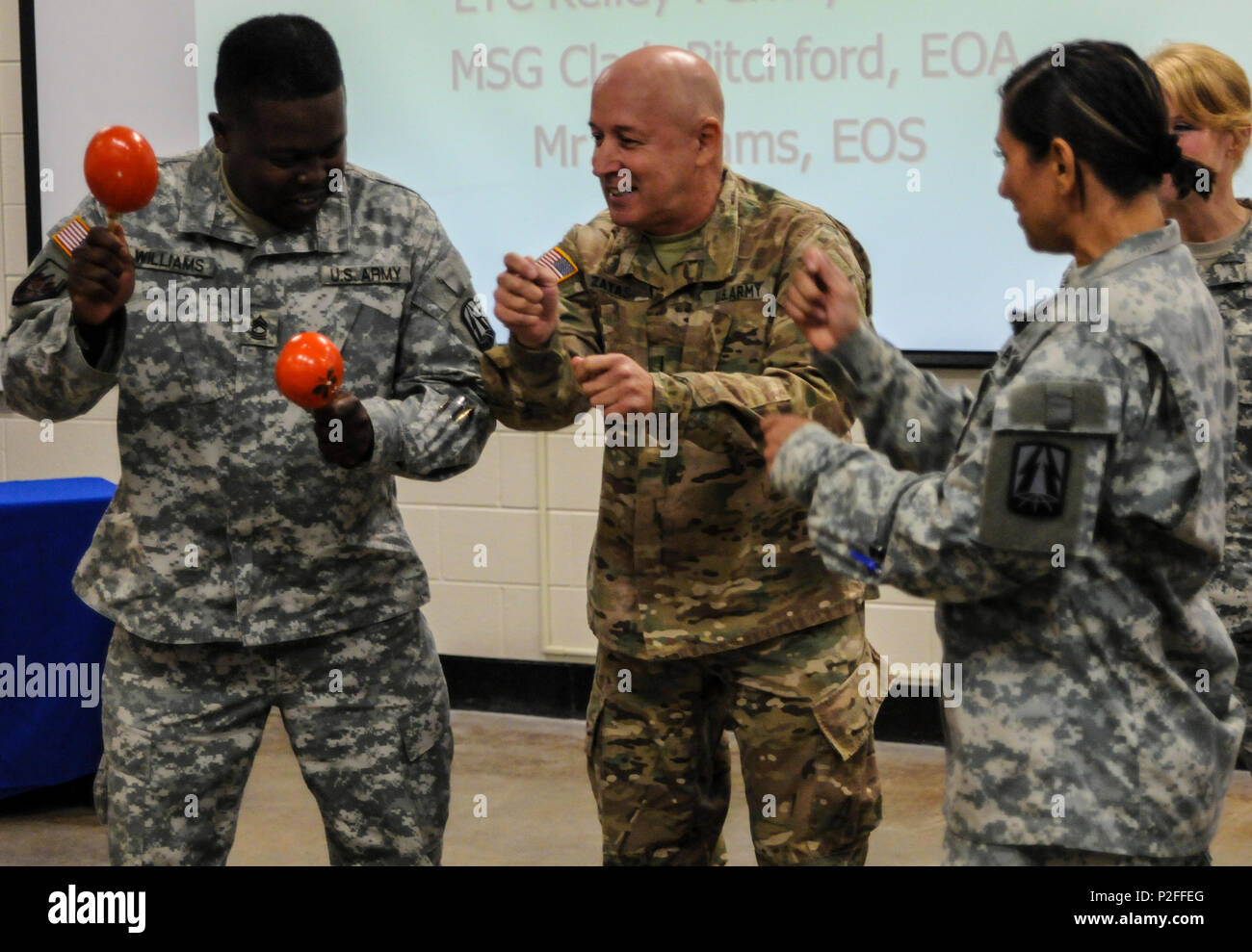 Chief Warrant Officer 5 Miguel Zayas, a Caguas, Puerto Rico native and G36 senior technical advisor, and Master Sgt. Marland Williams, the G1 noncommissioned officer in charge, both from the 335th Signal Command (Theater), discuss how to properly play the maracas during the Equal Opportunity Observance in East Point, Georgia Sept. 18, 2016. During battle assembly weekend, the Equal Opportunity Office conducted its annual observance of National Hispanic Heritage Month. (U.S. Army photo by Sgt. Stephanie A. Hargett) (Released) - Stock Image