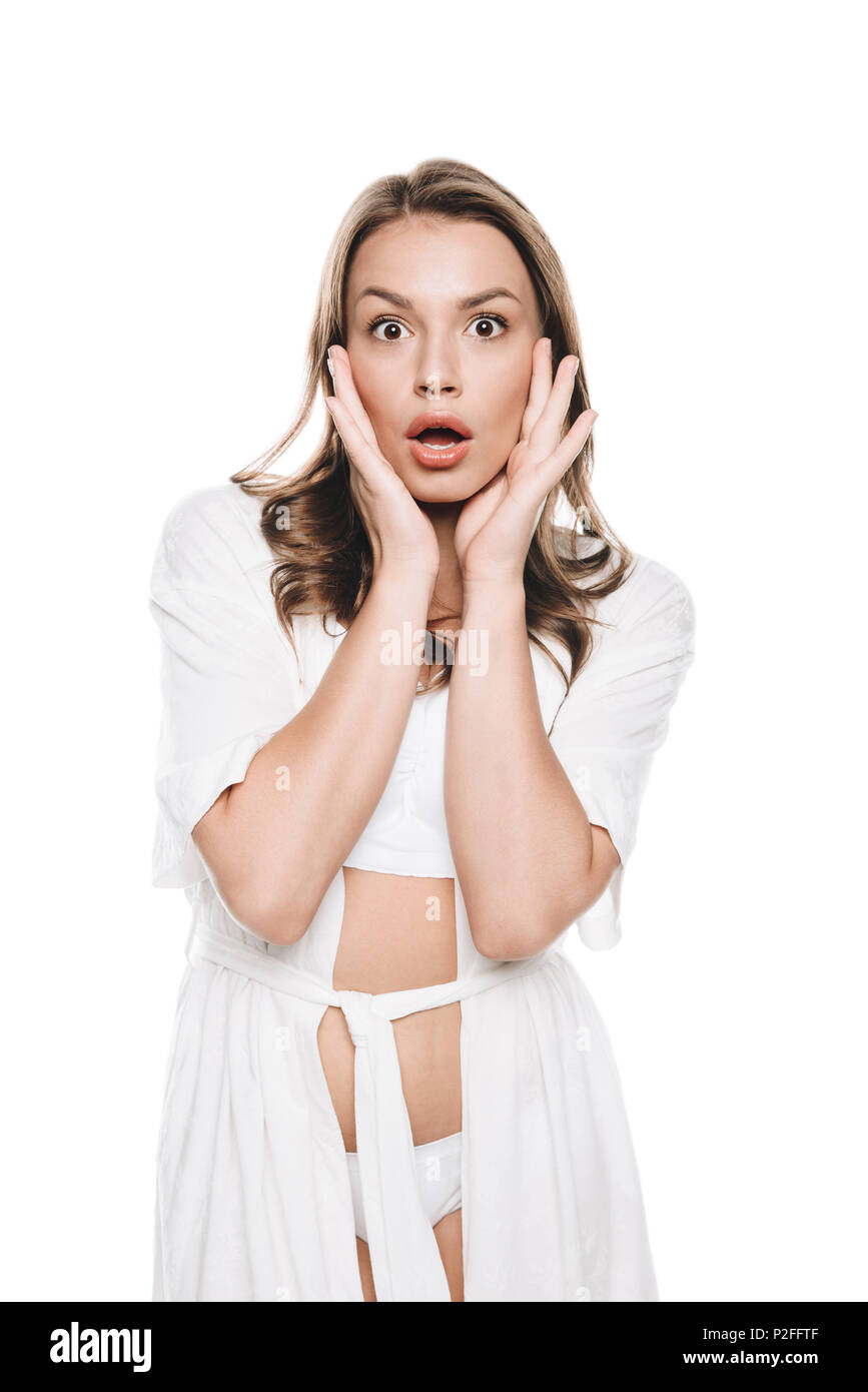 Portrait of woman in white robe gesturing with shocked expression looking at camera isolated on white - Stock Image