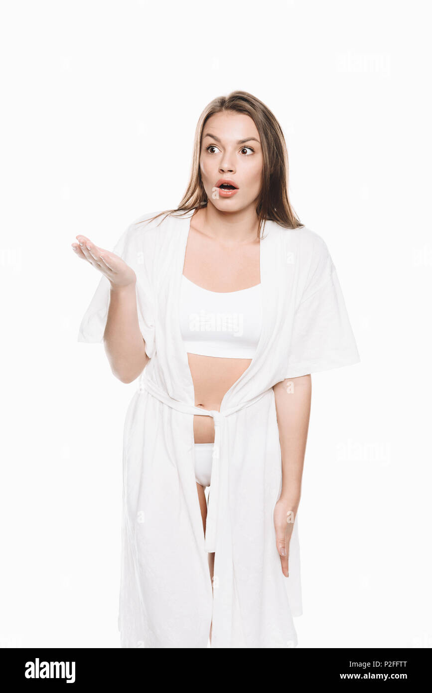 Portrait of young woman in white robe gesturing with shocked expression isolated on white - Stock Image