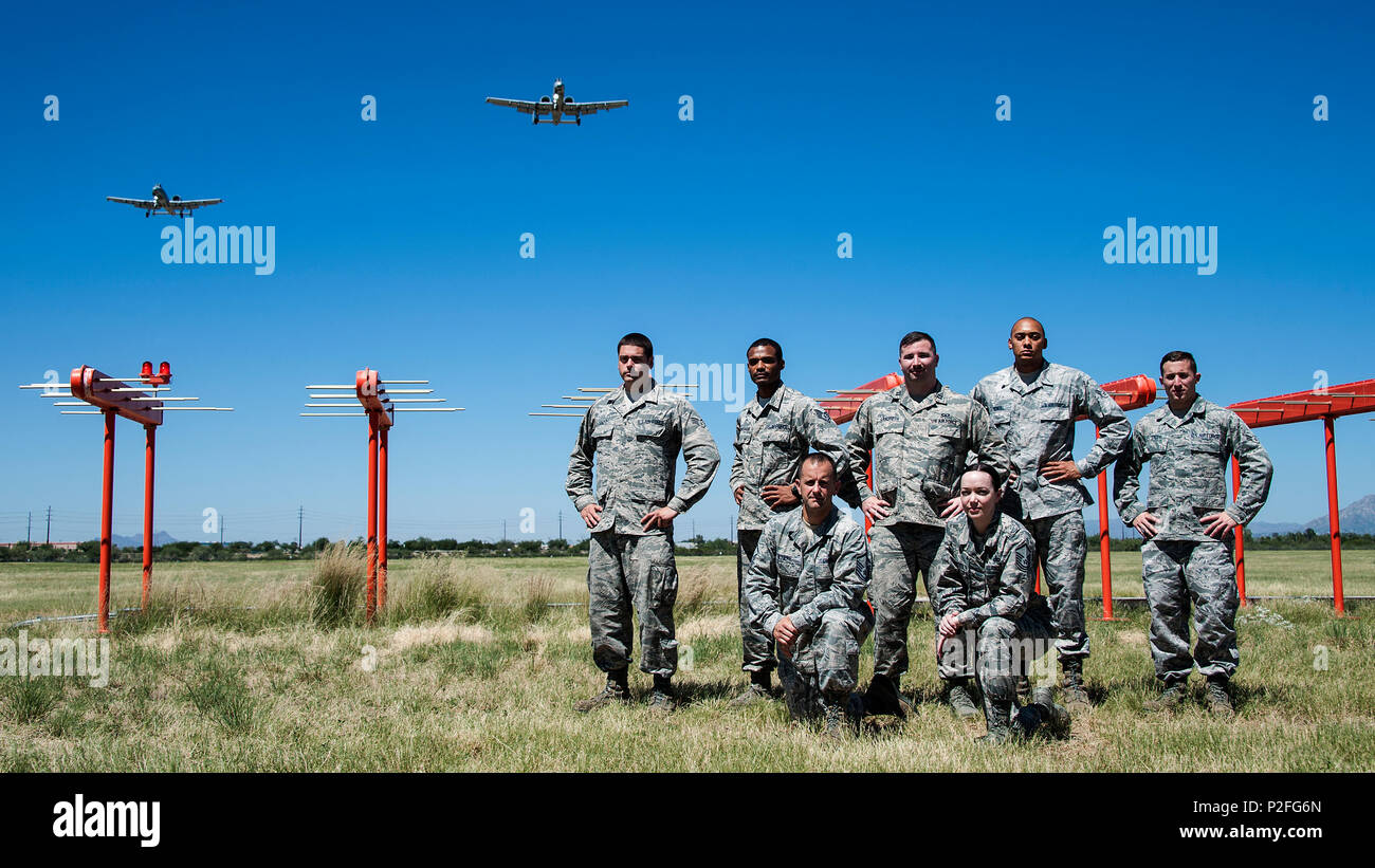 U.S. Airmen from the 355th Operations Support Squadron pose for a photograph in front of Runway 12's newly activated Instrument Landing System as two A-10C Thunderbolt II aircraft fly above Davis-Monthan Air Force Base, Ariz., Sept. 15, 2016. The ILS provides approaching aircraft with horizontal and vertical guidance relative to the centerline and the threshold of the runway for an accurate landing approach. (U.S. Air Force photo by Senior Airman Chris Drzazgowski) - Stock Image