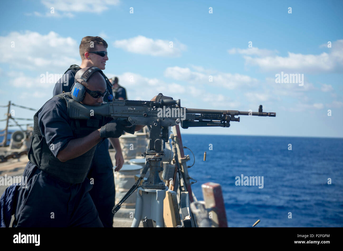 160907-N-DQ503-246  MEDITERRANEAN SEA (Sept. 7, 2016) Gunner's Mate 2nd Class John Murphy observes as Gunner's Mate 2nd Class Allen Marshall fires an M240B machine gun aboard the guided-missile destroyer USS Roosevelt (DDG 80) during a live-fire exercise. Roosevelt, deployed as part of the Eisenhower Carrier Strike Group, is supporting maritime security operations and theater security cooperation efforts in the U.S. 5th Fleet area of operations. (U.S. Navy photo by Mass Communication Specialist 3rd Class Taylor A. Elberg/Released) - Stock Image