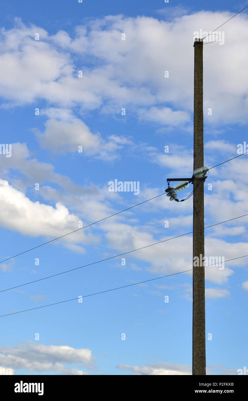 Concrete pole with wires of power line against the background of blue cloudy sky - Stock Image