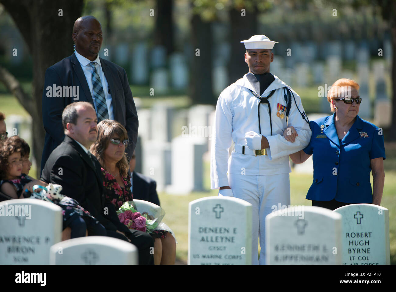 Arlington Lady Paula McKinley, right, and Seaman Andre Holloman, her escort,  participate in the graveside service for U.S. Navy Capt.
