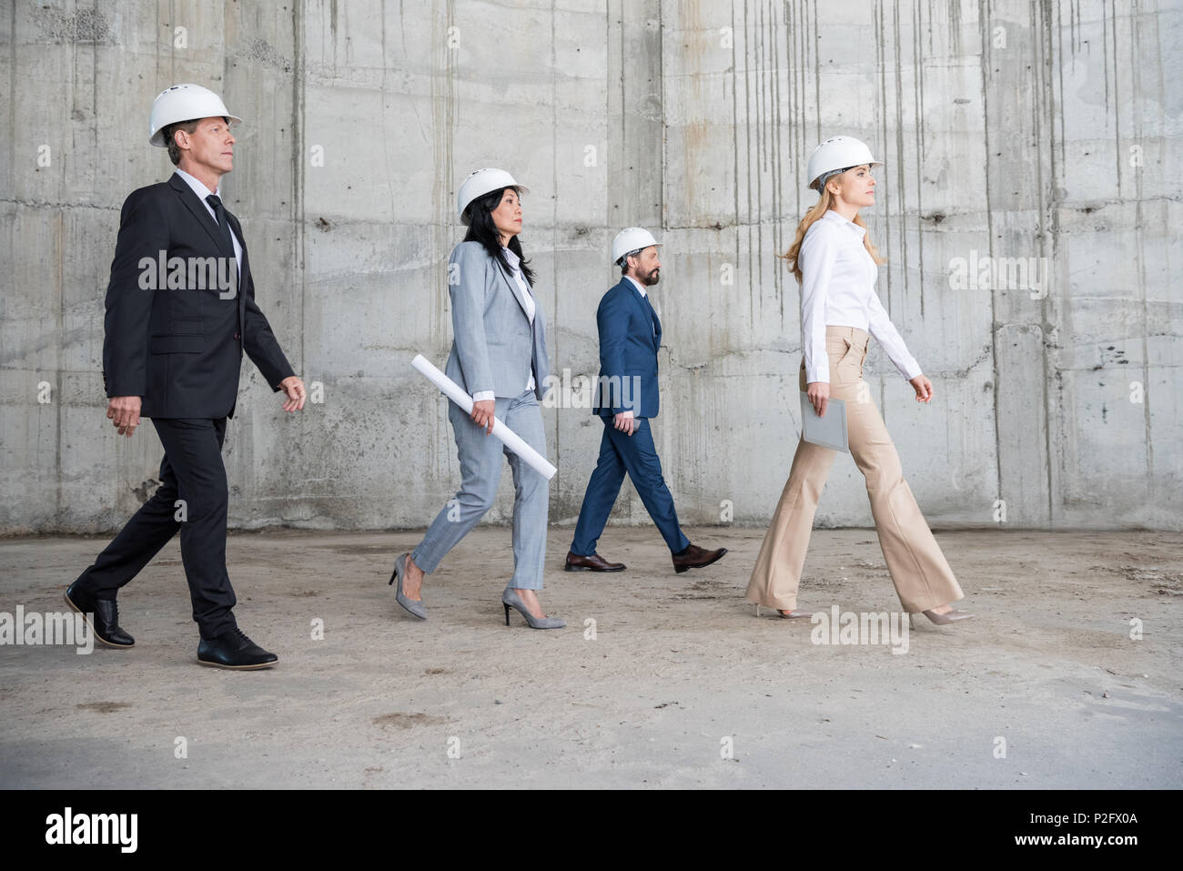 Group of professional architects in helmets holding blueprint and group of professional architects in helmets holding blueprint and walking at construction site malvernweather Images