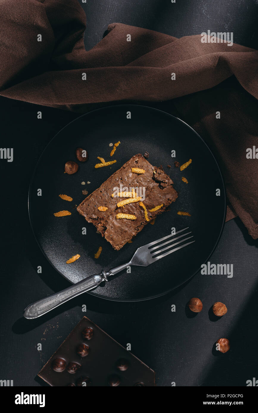 top view of delicious chocolate cake with orange zest on black plate - Stock Image