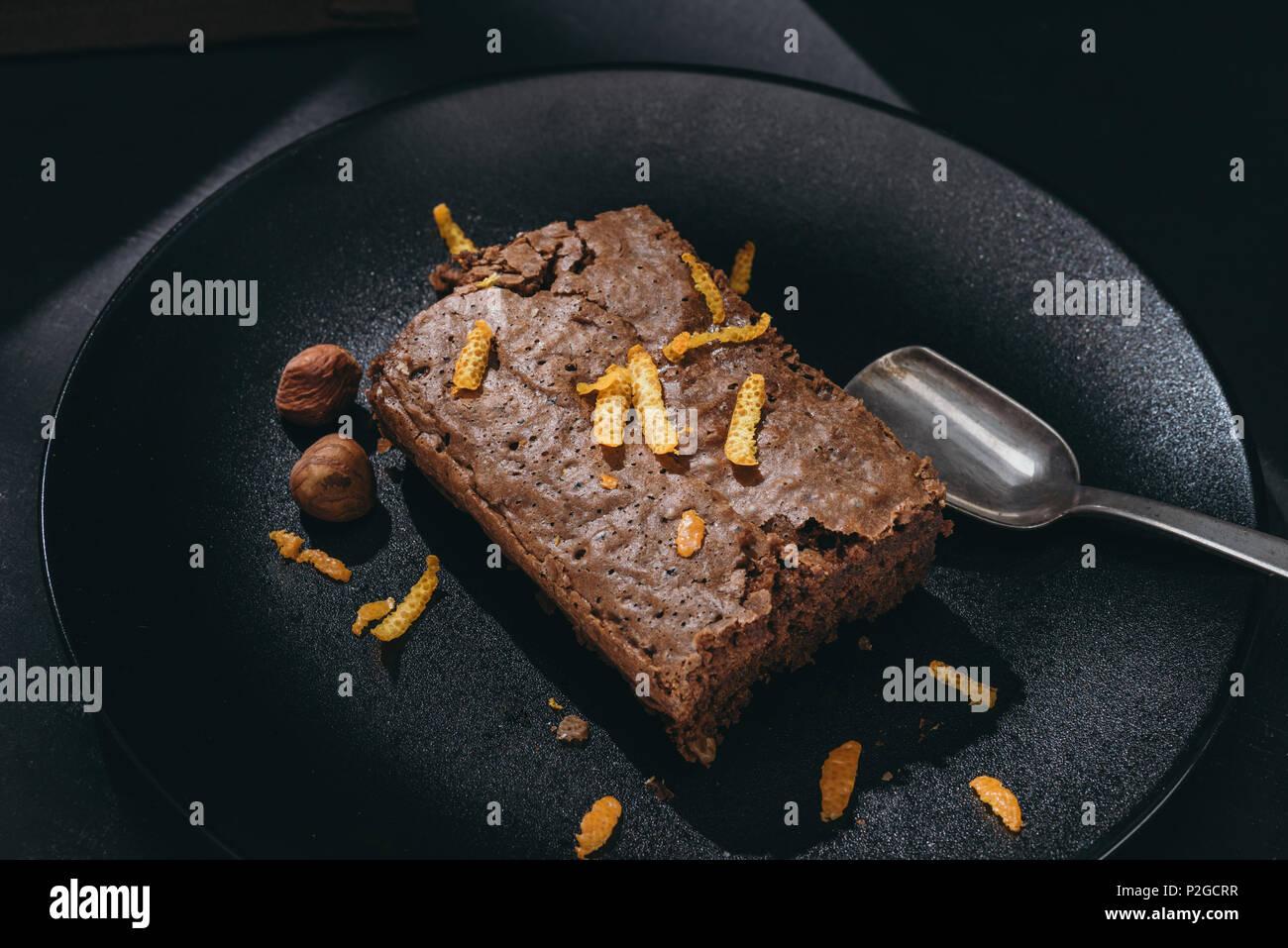 close-up shot of chocolate cake with orange zest on black plate - Stock Image