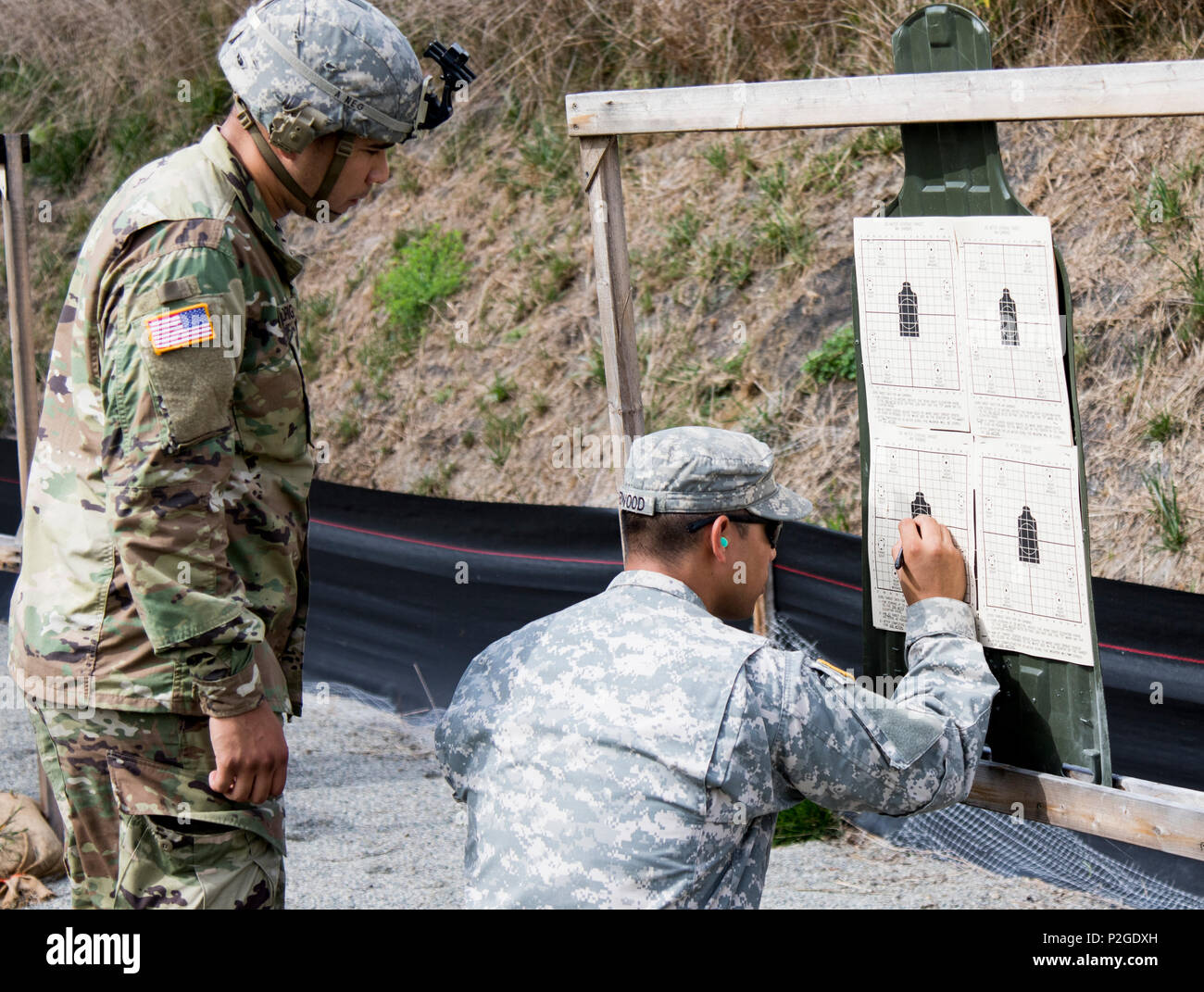 U.S. Army Spc. Ricardo Rodriguez, a light wheel vehicle mechanic assigned to the New York Army National Guard 145th Maintenance Battalion, reviews his zeroing score for the M4A1 on his target with range safety, Sgt. Julio Redwood, also with the 145th Maintenance Battalion, at Camp Smith Training Site, 20 September 2016. The Soldiers were qualifying in order to go on State Active Duty to reinforce Joint Task Force Empire Shield, the New York National Guard security force in New York City, at the direction of Governor Andrew M. Cuomo, in response to increased security concerns in the city follow Stock Photo