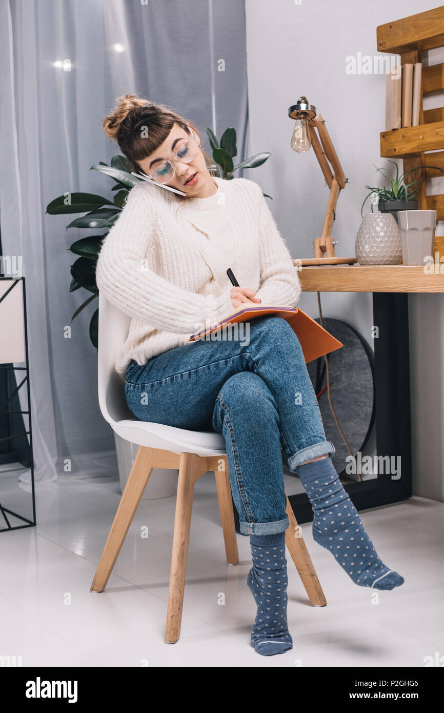 grimacing girl talking by smartphone and writing something to notebook in office - Stock Image