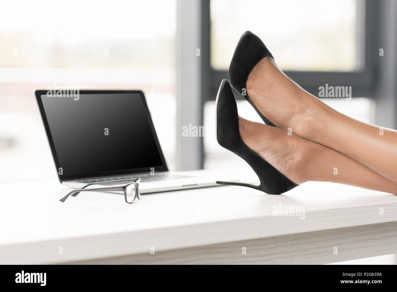 cropped shot of  businesswoman legs crossed on table near laptop and eyeglasses - Stock Image