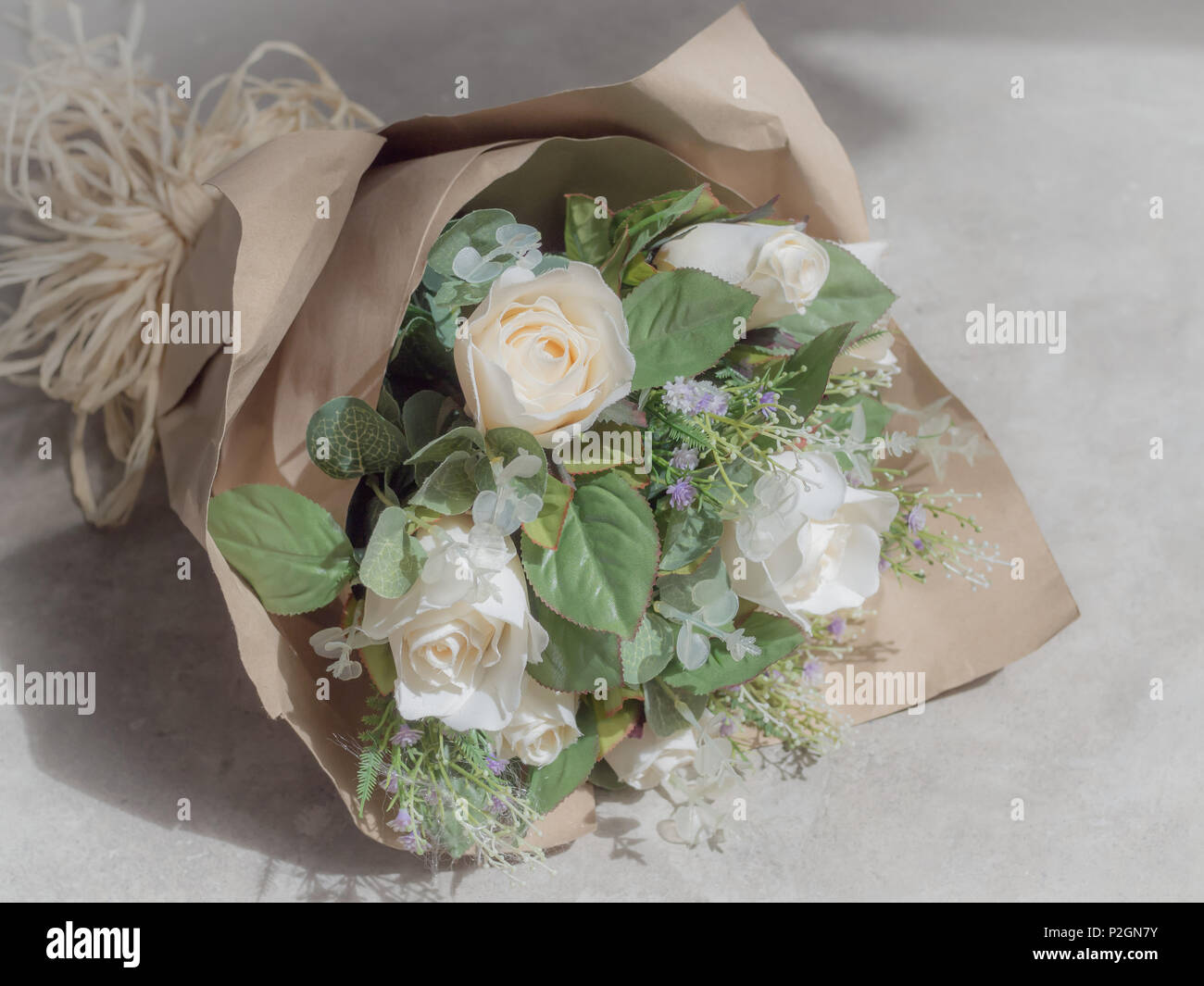 Artificial white roses bouquet in wrapping brown craft paper on artificial white roses bouquet in wrapping brown craft paper on concrete background mightylinksfo
