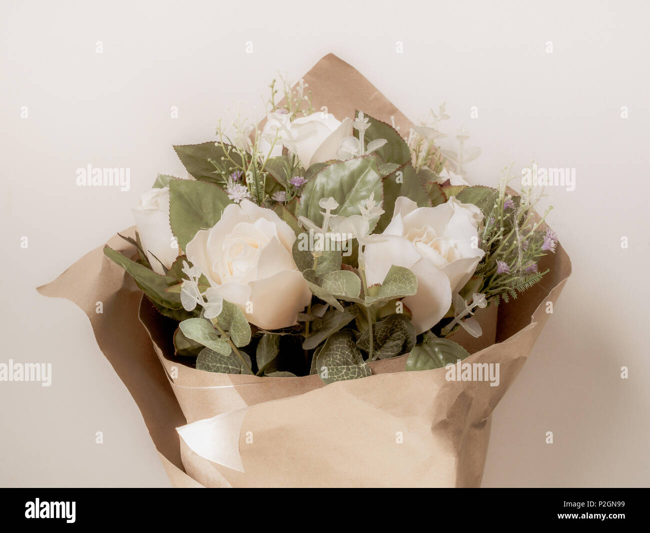 Artificial white roses bouquet in wrapping brown craft paper isolate artificial white roses bouquet in wrapping brown craft paper isolate on white background with space mightylinksfo