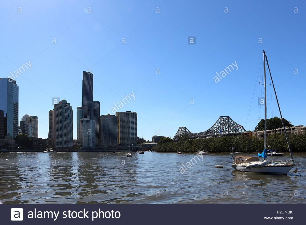 Sailing boats in front of Story Bridge and skyscrapers under blue skies in Brisbane, Australia - Stock Image