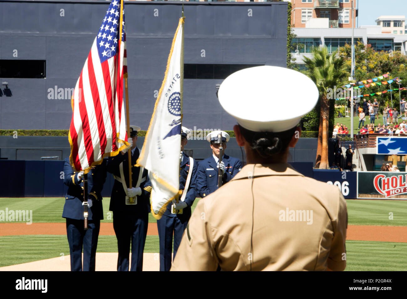 A color guard team from Coast Guard Sector San Diego presents the colors while Marine Private First Class Senora Lyons sings the National Anthem, Sept. 25, 2016, at the San Diego Padres vs. San Francisco Giants baseball game at Petco Park, San Diego, Calif. Every Sunday home game is military appreciation day at Petco Park, and servicemembers from the Navy, Coast Guard and Marine Corps perform the opening ceremony and during the 7th inning stretch. (U.S. Marine Corps photo by Lance Cpl. Adam Dublinske) - Stock Image