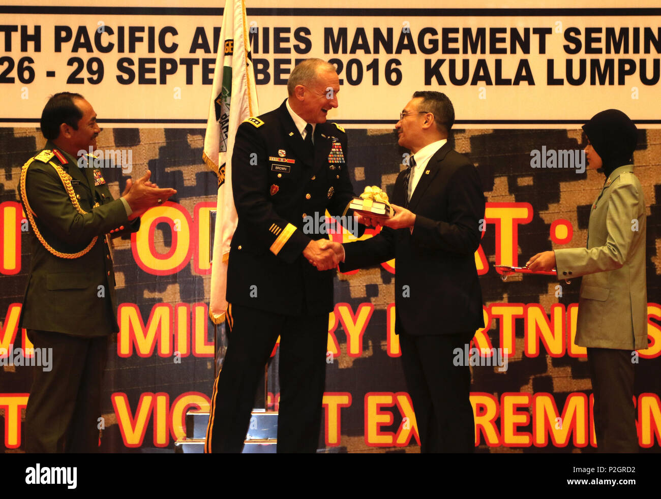 "U.S. Army Gen. Robert B. Brown, Commander, U.S. Army Pacific and Lt. Gen. Dato' Sri Zulkiple, Field Commander West, Malaysian Army present a memento to the Honorable Dato' Seri Hishmuddin, Minister of Defence Malaysia during the opening ceremony for PAMS 2016, in Kuala Lumpur, Malaysia, September 26. PAMS is an annual multinational military seminar providing a forum for senior level ground force officers from regional ground forces and security forces to meet, exchange views and discuss professional military subjects. This year's theme is ""Unity of Effort: Building Civil-Military Partnerships  Stock Photo"
