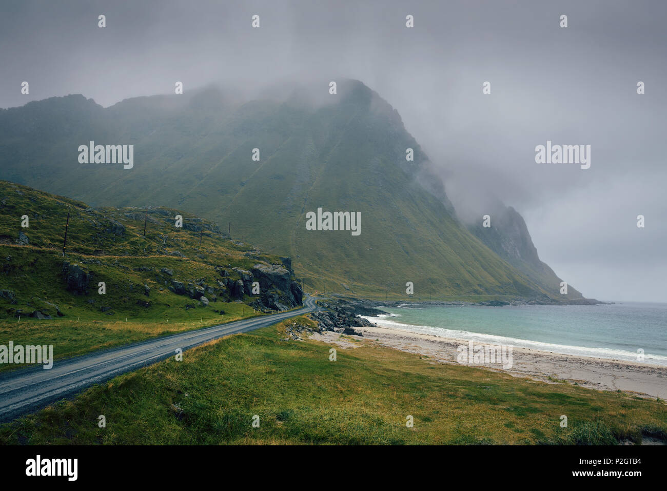 Scenic road along the coastline in Norway on a rainy and foggy day - Stock Image