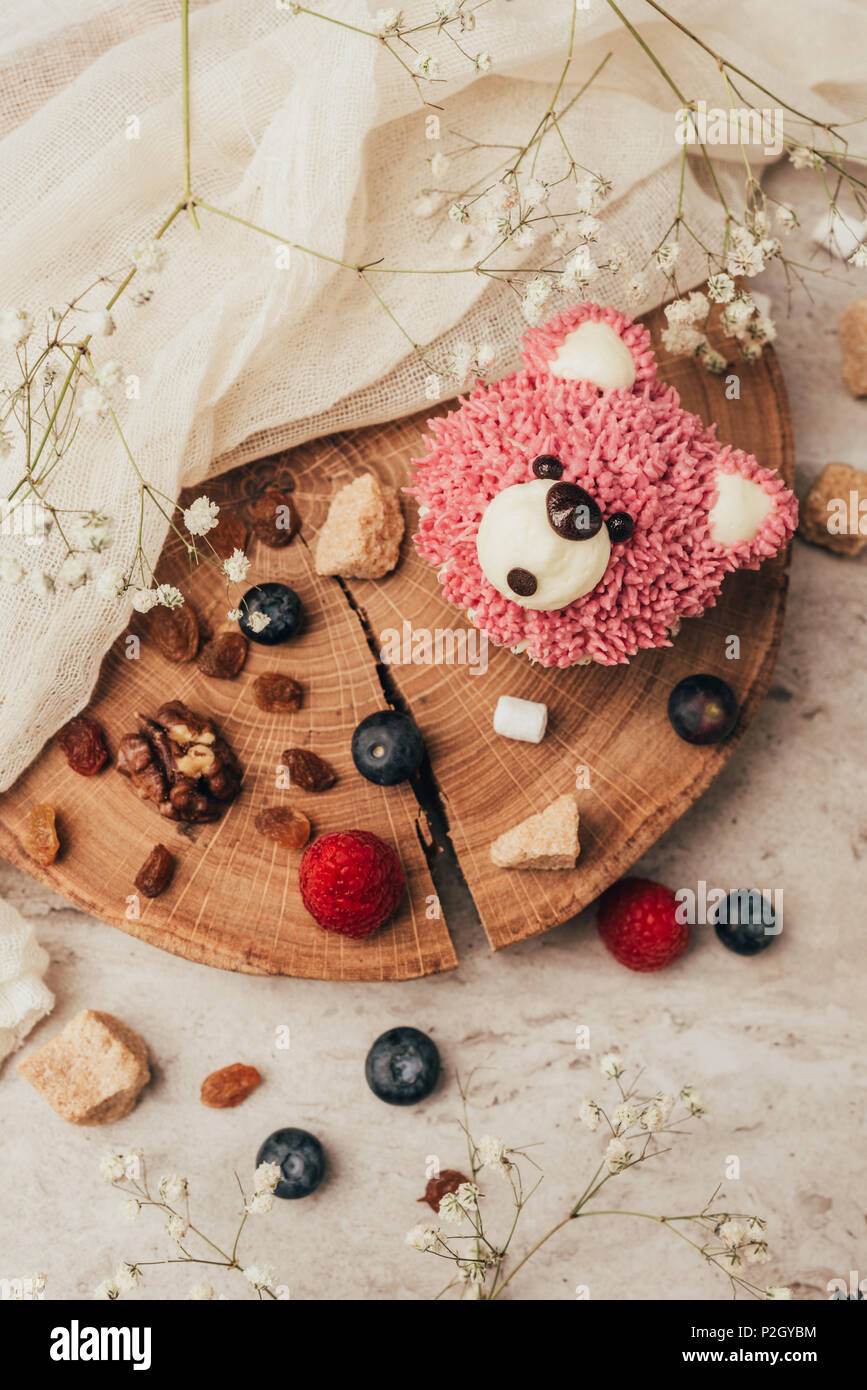 top view of delicious muffin in shape of bear with berries on wooden board - Stock Image
