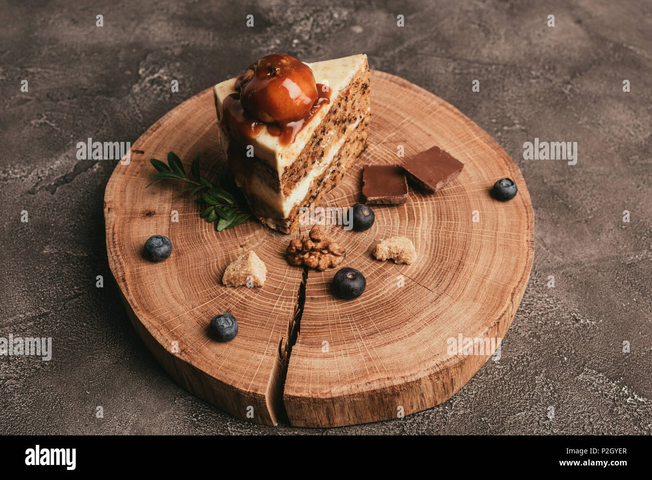 delicious piece of cake with chocolate and blueberries on wooden board - Stock Image