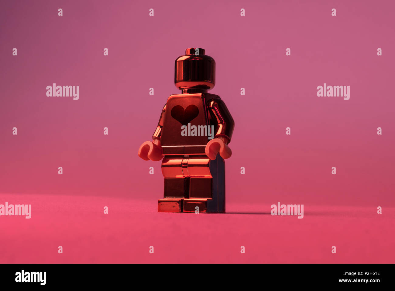 A big shiny lego toy man or woman with a big heart, ready for love, be my valentine - Stock Image