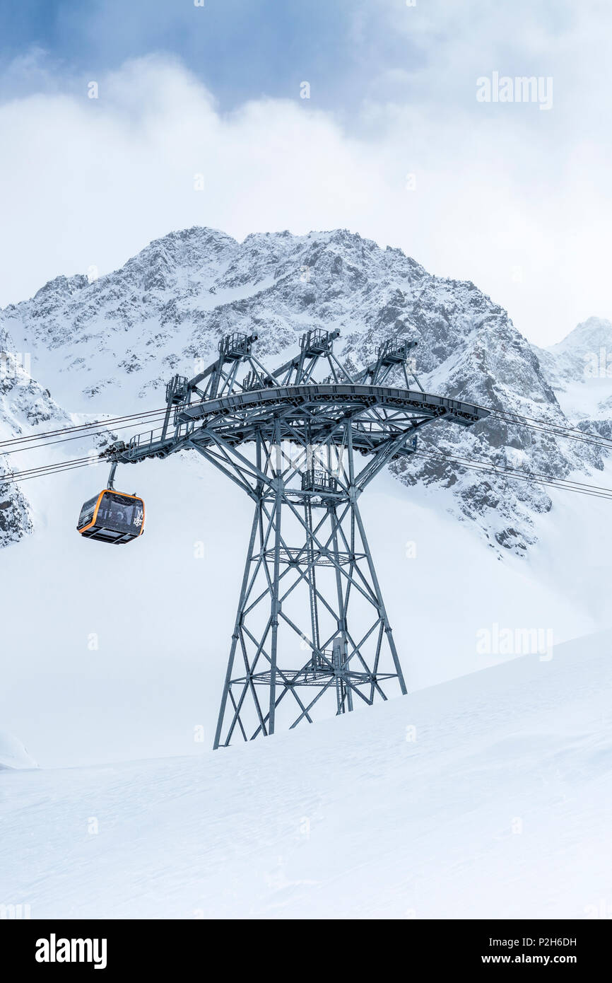 Gondola of cableway at Stubai Glacier ski resort with snowy mountains as background, Neustift im Stubaital, Austrian Alps, Tyrol, Austria - Stock Image