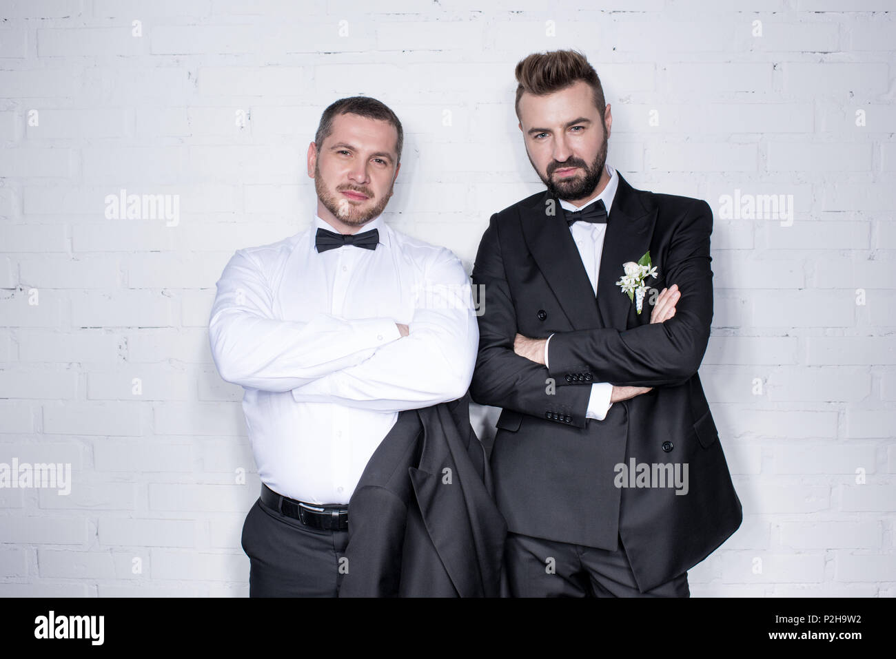Couple of grooms in tuxedos looking at camera and posing with arms crossed - Stock Image