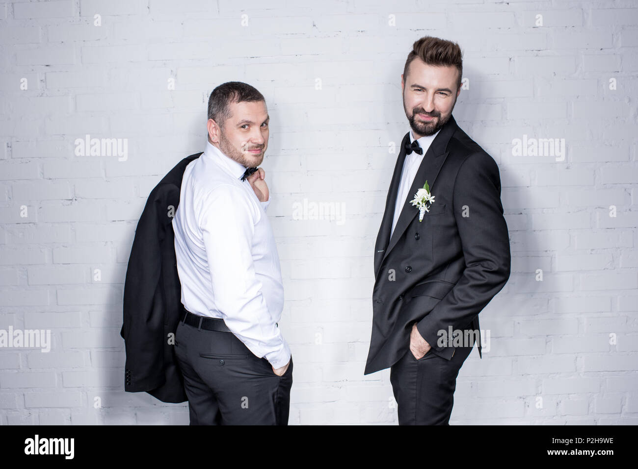 smiling couple of grooms in tuxedos posing during wedding day - Stock Image