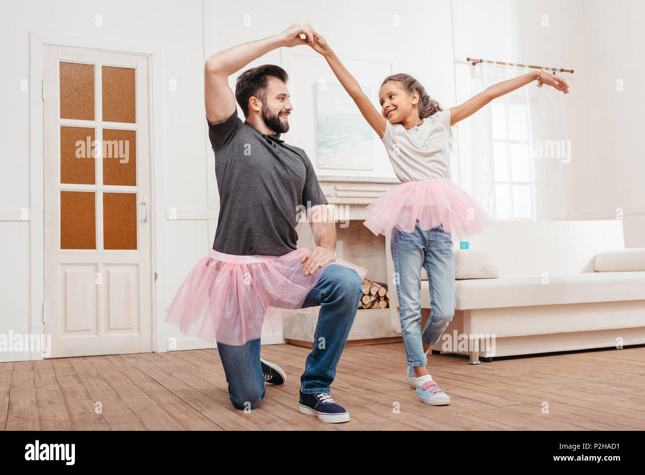 b1980a26ea multicultural father and daughter in pink tutu tulle skirts dancing at home  - Stock Image