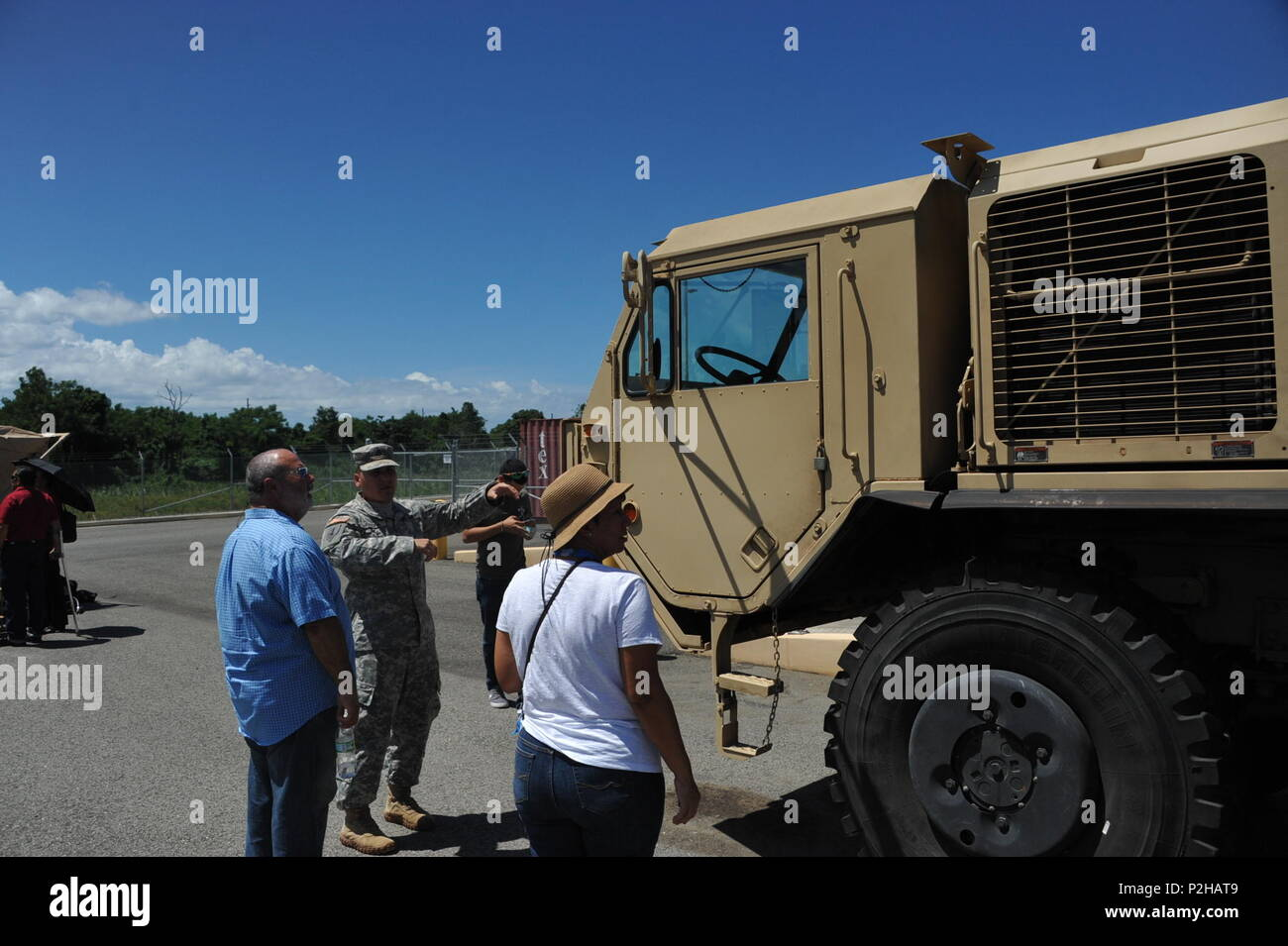 Sgt. Nathaniel Rivera informs his mother-in-law and father-in-law of the purpose of the vehicles on exhibit after the 246th Quartermaster Co. (MA) farewell ceremony at the Army Reserve Center at Mayaguez, PR. - Stock Image