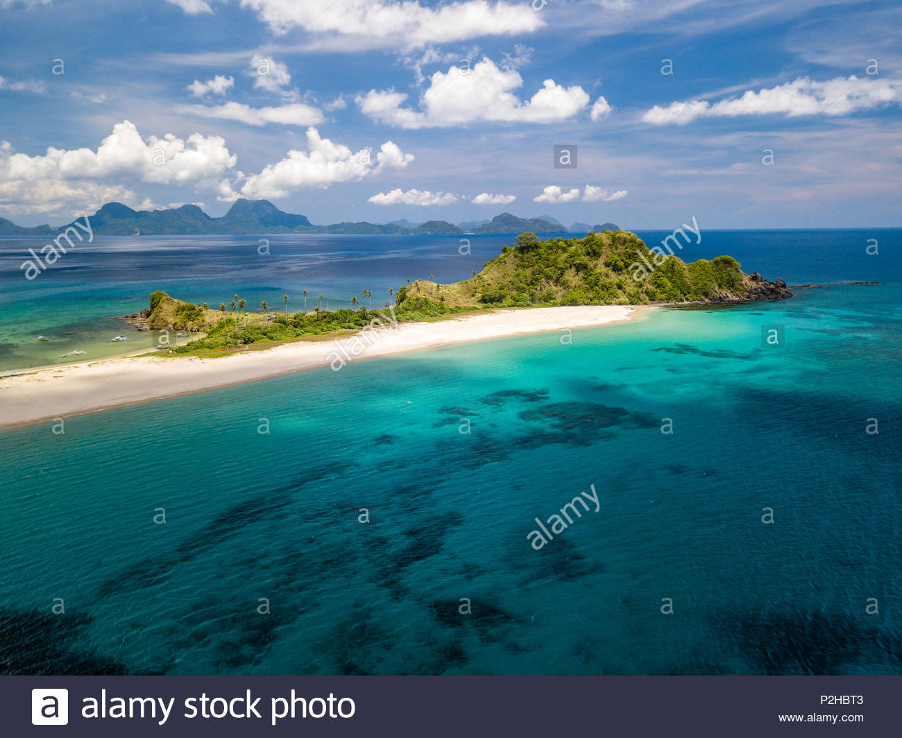 Aerial drone view of an empty, beautiful tropical beach surrounded by coral reef and greenery (Nacpan Beach, Palawan) - Stock Image