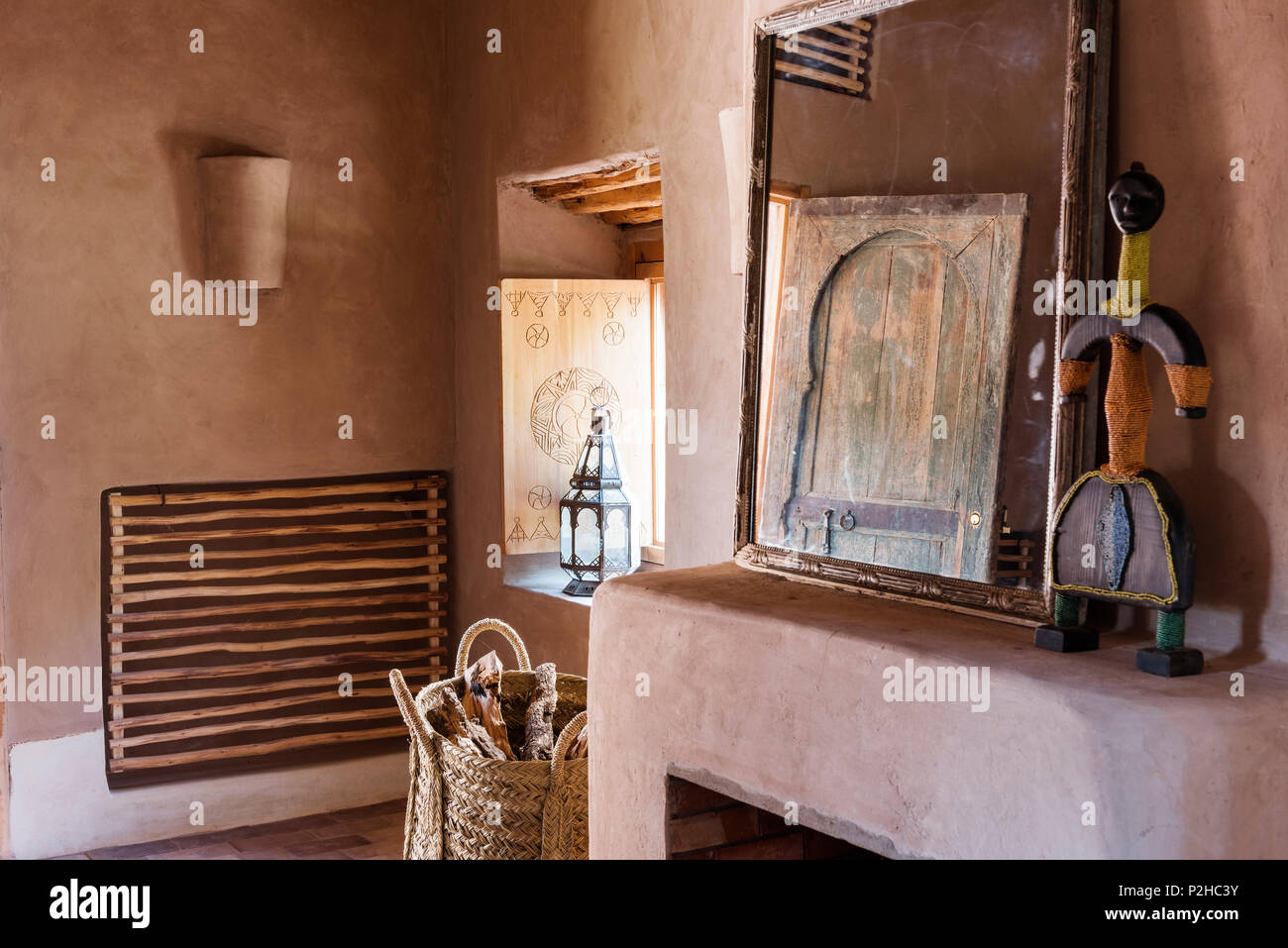 Rattan fire basket by open fireplace in bedroom woth earth walls and terracotta floors. A mirror and African folk art statue adorn the mantelpiece - Stock Image