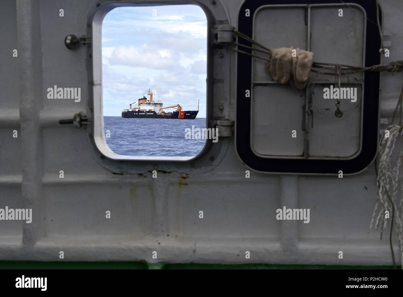 The U.S. Coast Guard buoy tender USCGC Sequoia (WLB-215) maintains position off the port beam of the fishing vessel Ayamaru No. 58 while a boarding team conduct a fisheries enforcement boarding on the vessel in the Palau exclusive economic zone Sept. 3, 2016. The Coast Guard, working with the Palau National Police conducted fisheries enforcement boardings in the Palau EEZ under a bilateral agreement. (U.S. Coast Guard photo by Chief Petty Officer Sara Mooers) - Stock Image