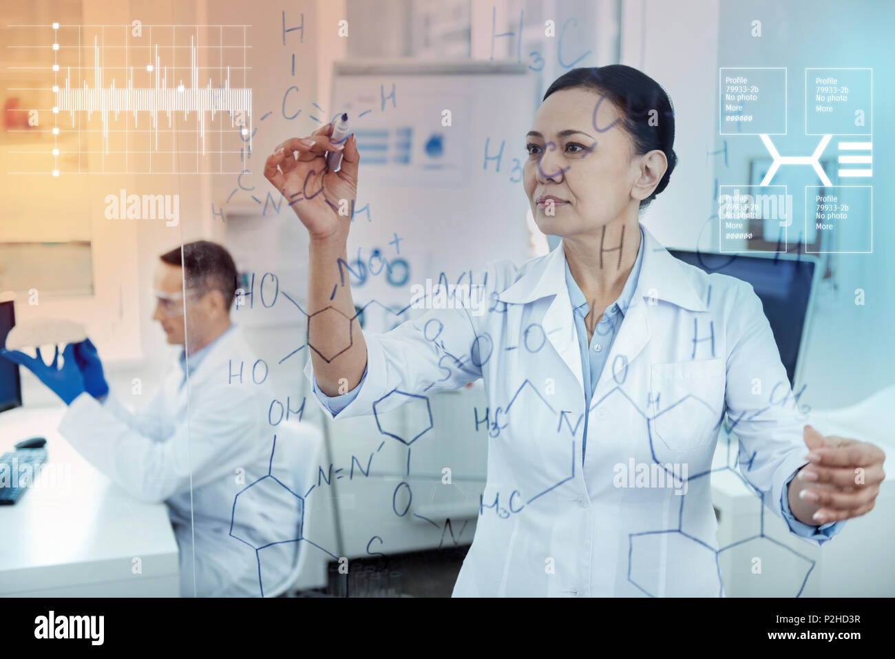 Calm chemist looking concentrated while writing on the transparent board - Stock Image