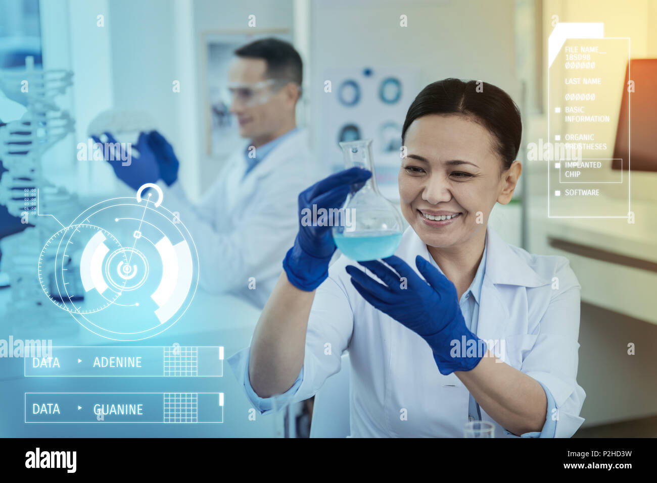 Happy scientist smiling while looking at the blue liquid - Stock Image