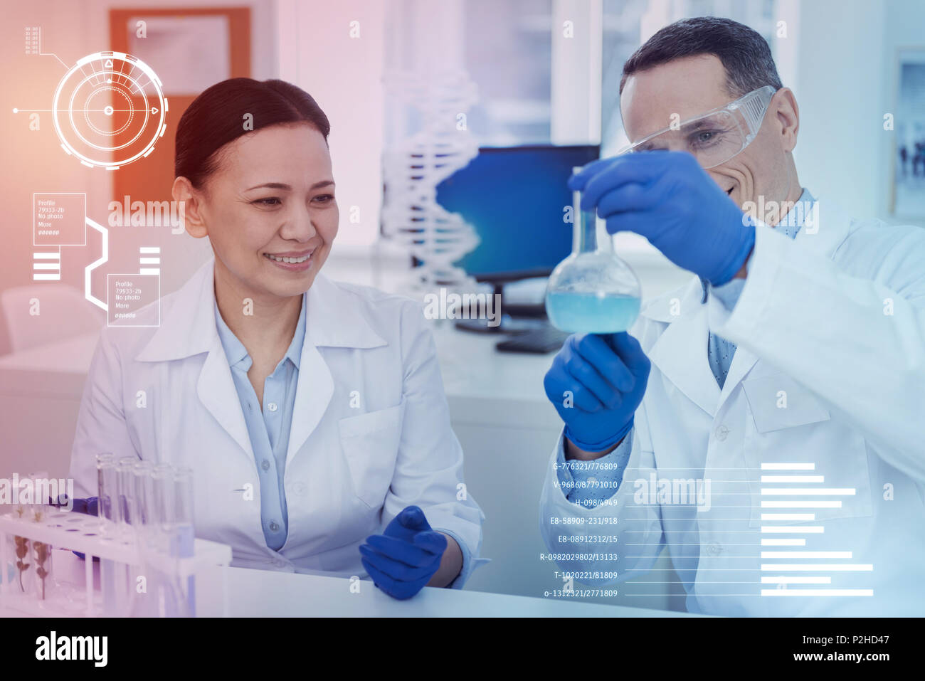 Positive scientist looking at the liquid in a bottle and smiling happily - Stock Image