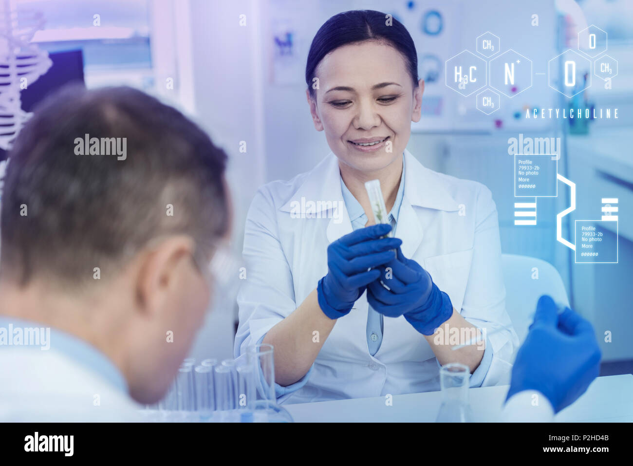 Calm biologist smiling while looking at the herb in a test tube - Stock Image