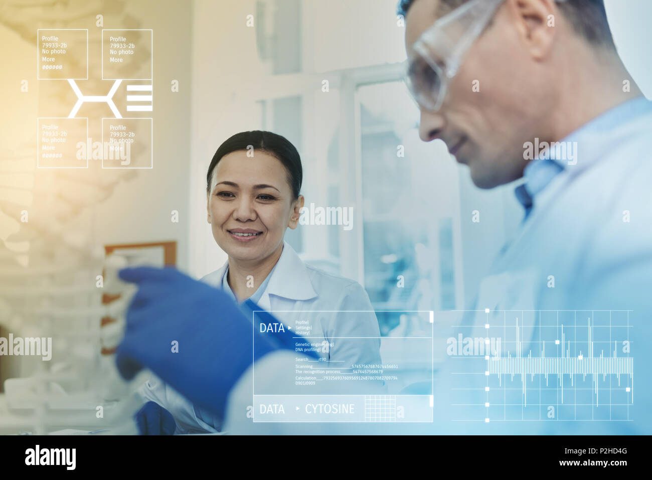 Cheerful biologist sitting in a lab and studying cell chains - Stock Image