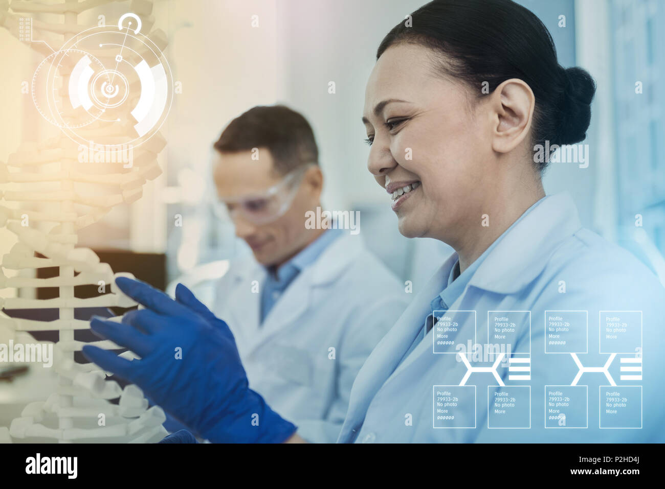 Positive biologist wearing gloves and looking at the DNA model - Stock Image
