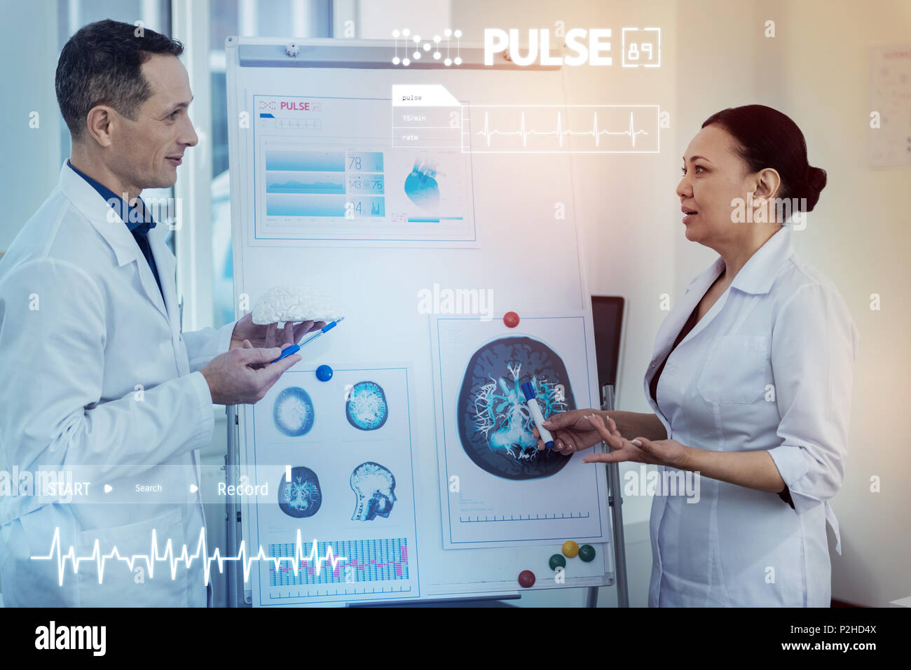 Serious doctors standing near the flipchart and discussing the brain - Stock Image