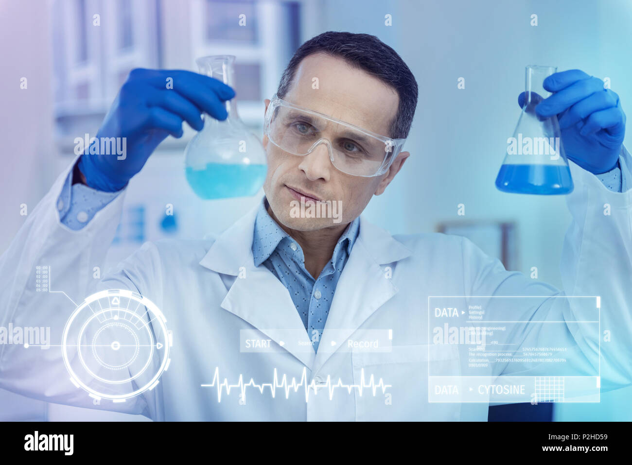 Careful scientist looking interested while comparing two liquids - Stock Image