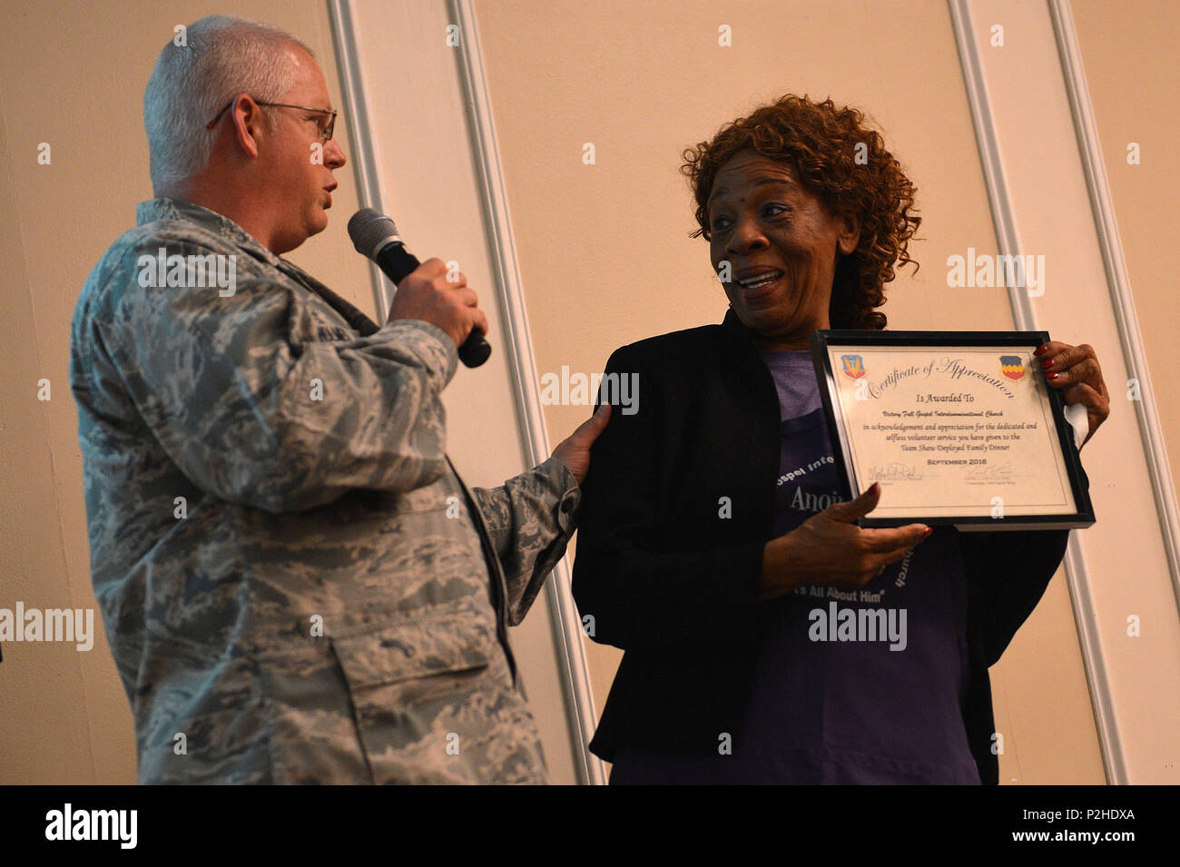 U.S. Air Force Chaplain (Maj.) Richard Holmes, 20th Fighter Wing chaplain, presents Joann Murrill, Victory Gospel Interdenomination Church pastor, with a certificate of appreciation during a deployed family dinner at the Carolina Skies Club and Conference Center at Shaw Air Force, S.C., Sept. 26, 2016. Murrill was recognized for providing the evening meal for the event. (U.S. Air Force photo by Airman 1st Class Christopher Maldonado) - Stock Image