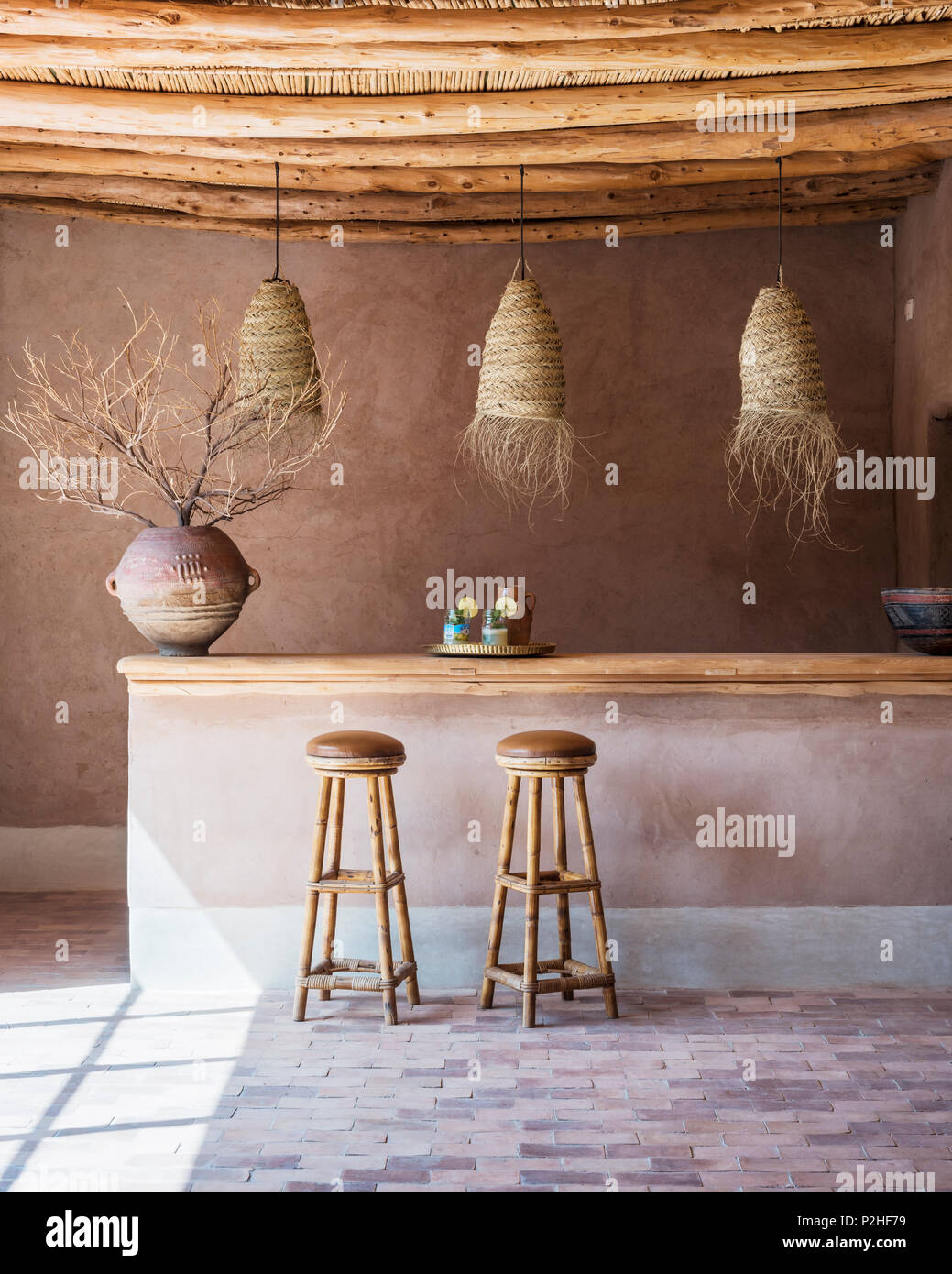 Rattan Lanterns Hang Above Counter With Bamboo Bar Stools In Bar With Wood Ceiling And Terracotta Floor The Antique Pot Comes From East Africa Stock Photo Alamy