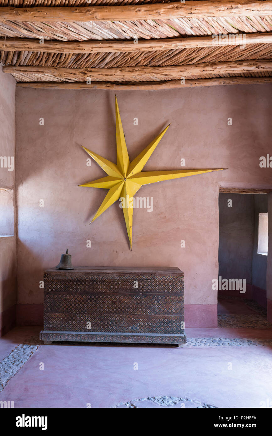 Large yellow star hung on earth wall in entrance hall of Berber Lodge with antique wooden chest and studded panelled door Stock Photo