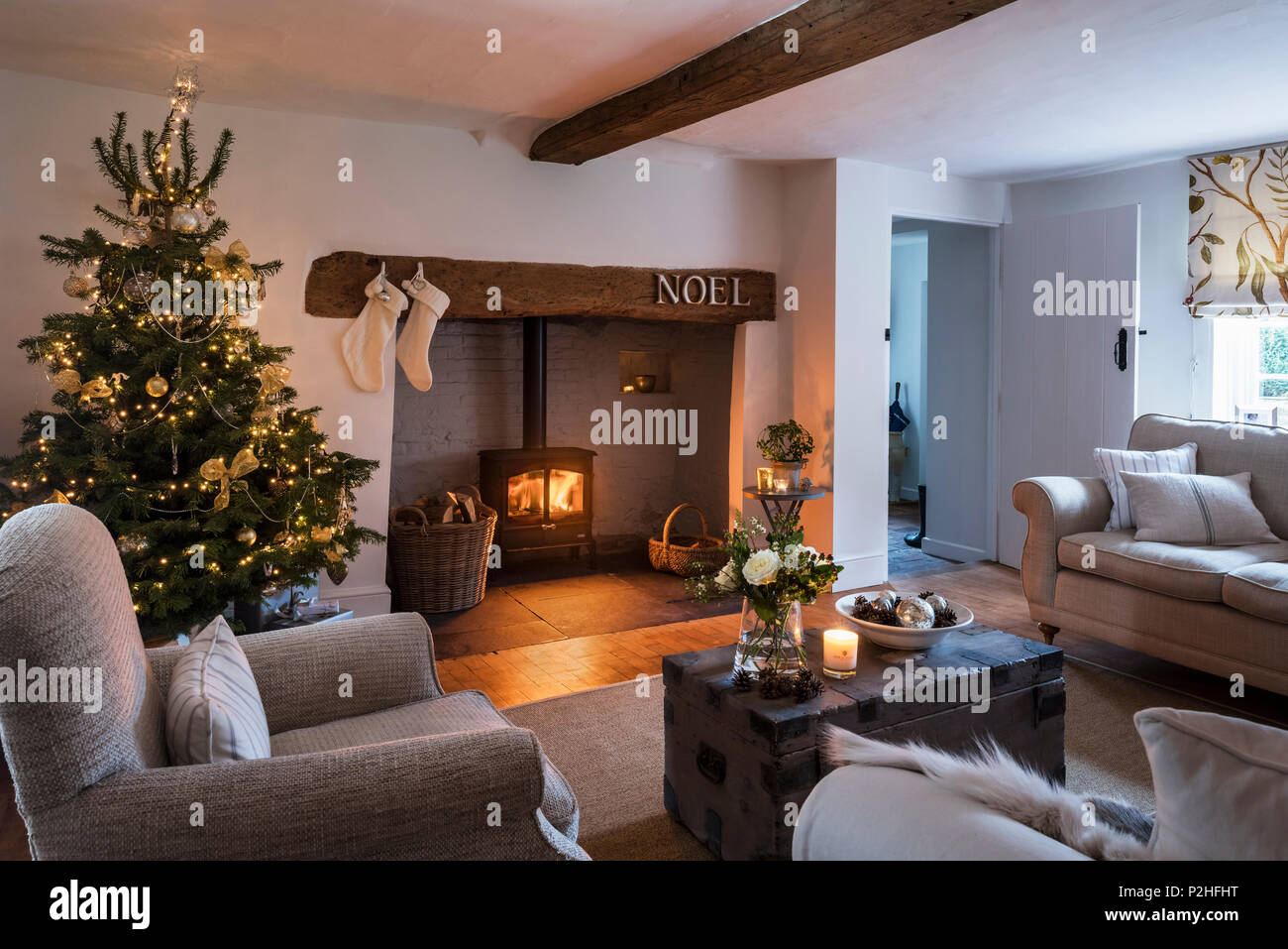 Cosy festive sitting room with inglenook fireplace and christmas tree, the sofa is by Laura Ashley and the blind in Lewis & Woods Adam's Eden fabric - Stock Image
