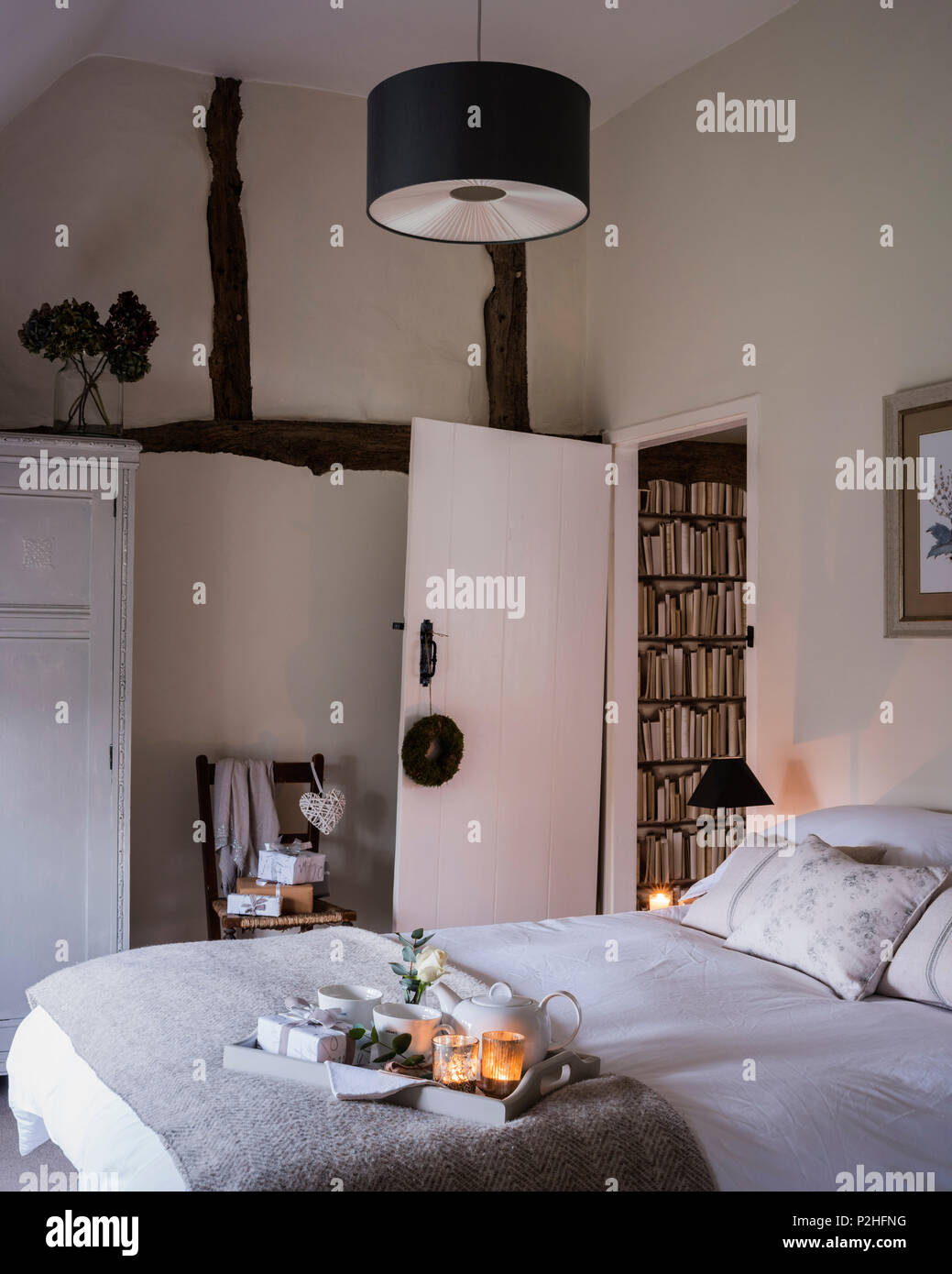 Guest bedroom with original beams and walls painted in Slipper satin by farrow & Ball. The throw is from Neptune - Stock Image