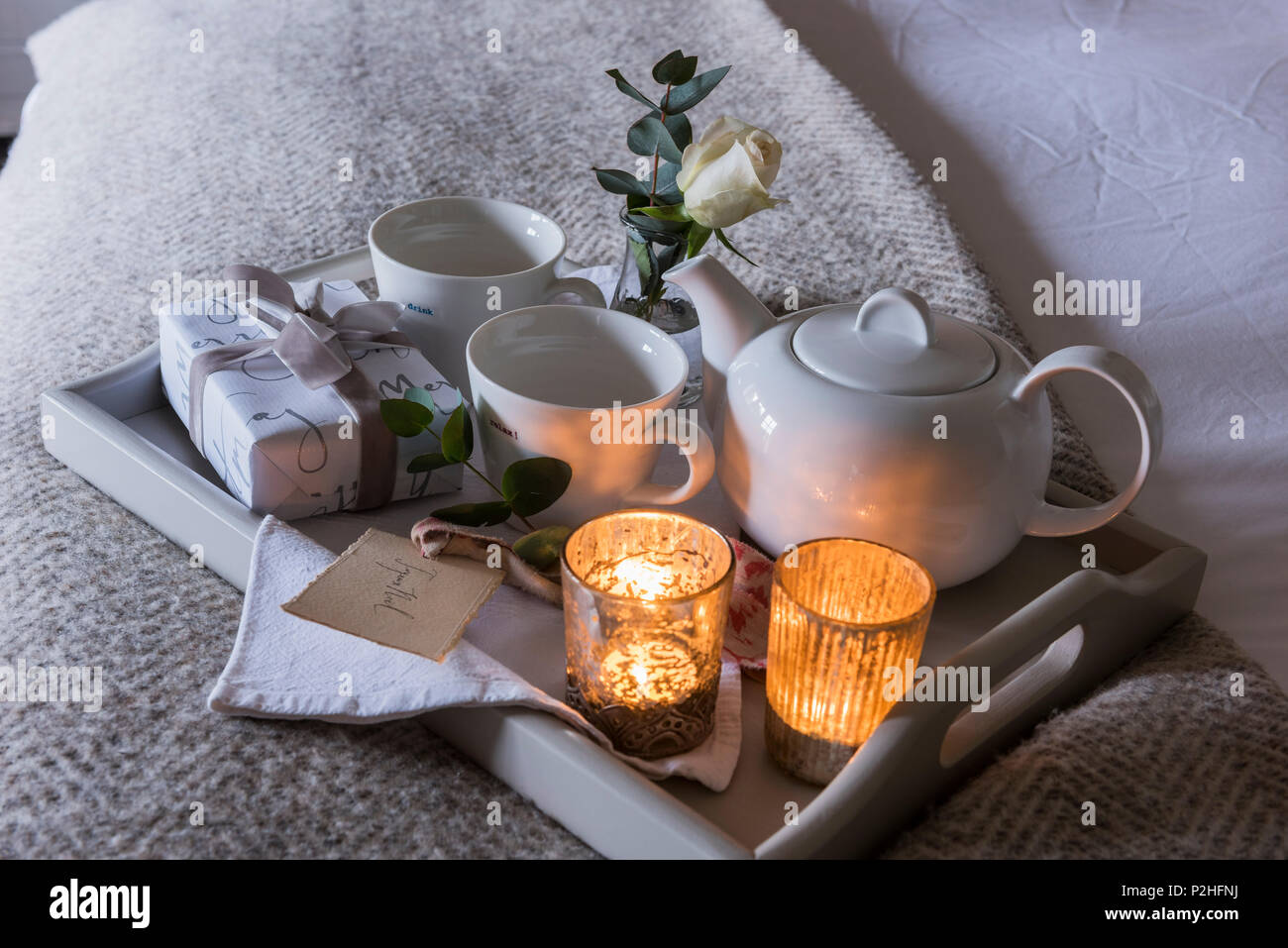 Detail of a tealight lit breakfast tray with small wrapped present and white rose. - Stock Image