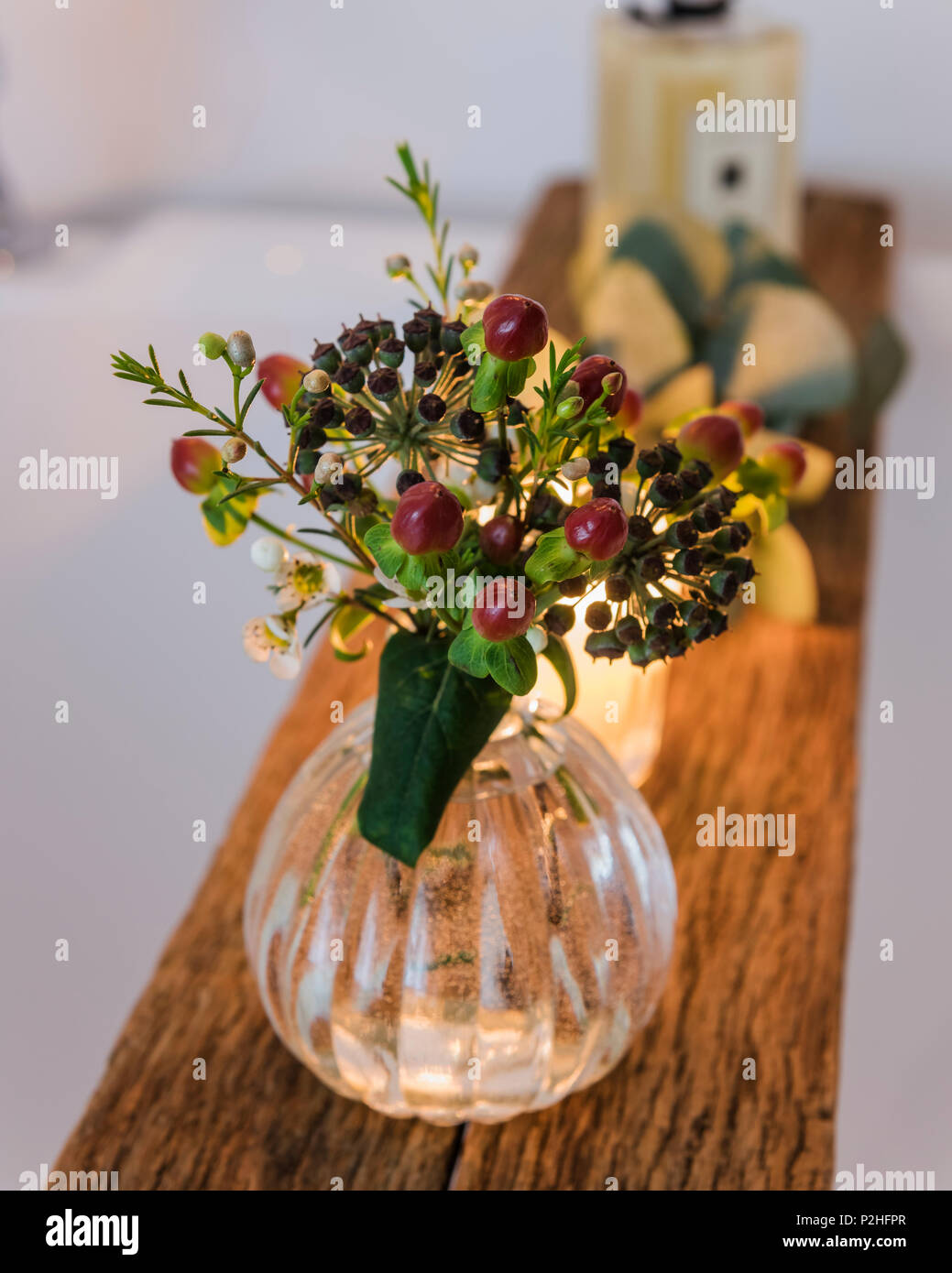 Small posey of berries on a wooden bath shelf. - Stock Image