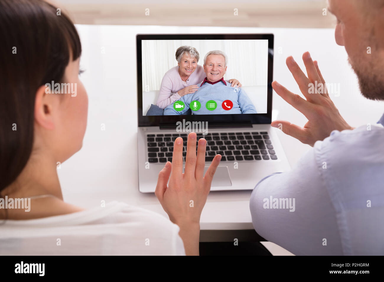 Close-up Of A Couple Video Conferencing With Parents On Laptop - Stock Image