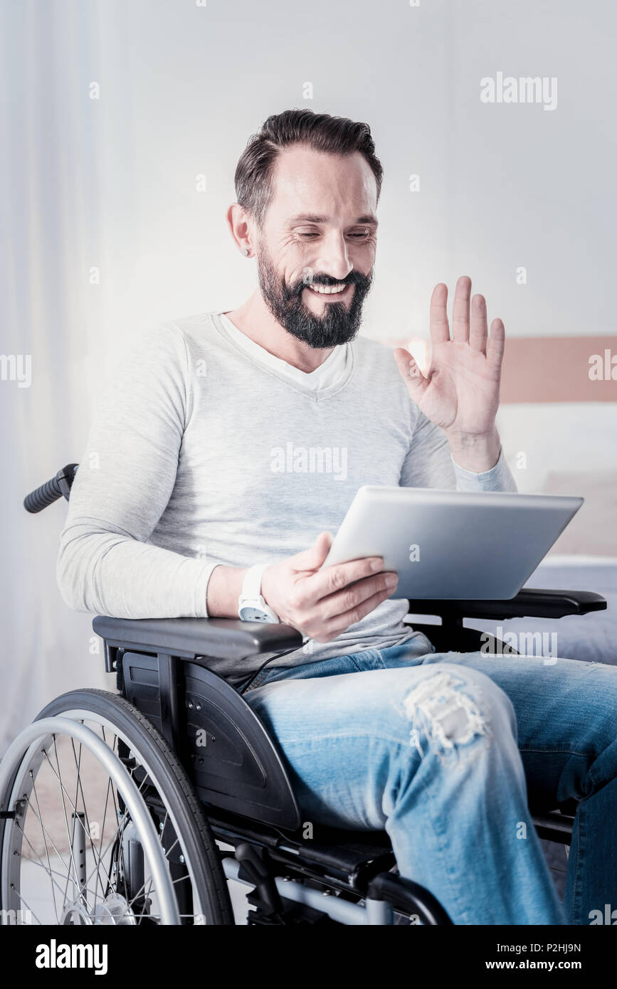 Happy disabled man talking with friends - Stock Image