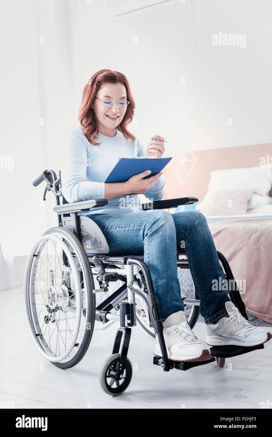 Cheerful crippled freelancer doing her work - Stock Image