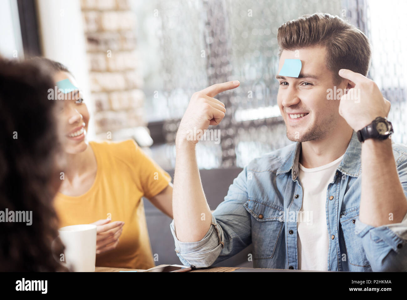 Nice joyful man pointing at the note - Stock Image